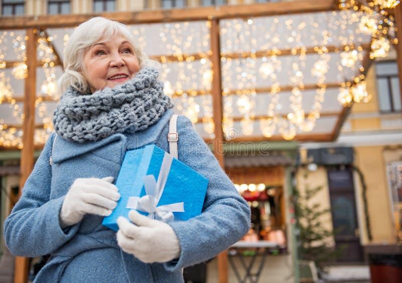 Εύθυμη ηλικιωμένη κυρία που στέκεται με το κιβώτιο δώρων στην οδό στοκ εικόνες με δικαίωμα ελεύθερης χρήσης