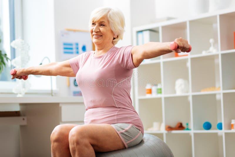 Εύθυμη θετική γυναίκα που κάνει τις ασκήσεις με τους αλτήρες στοκ εικόνα