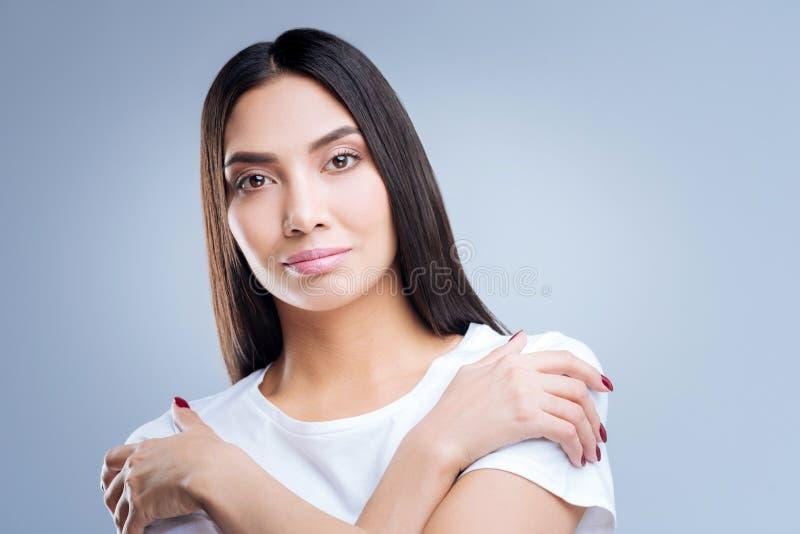 Εύθυμη καλή γυναίκα που χαμογελά φορώντας τα νέα ενδύματα στοκ φωτογραφίες