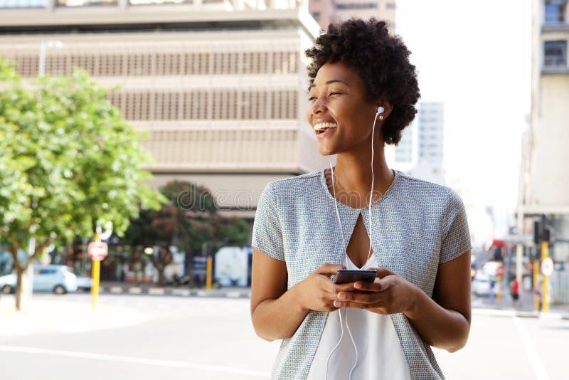 Εύθυμη κυρία έξω στην οδό πόλεων που ακούει τη μουσική στοκ φωτογραφία