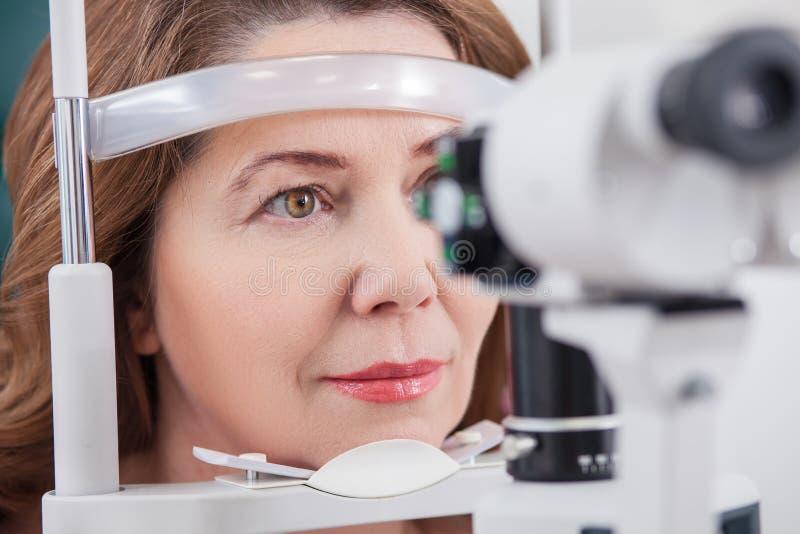 Εύθυμη κυρία που έχει την εξέταση ματιών στο γραφείο οφθαλμολόγων στοκ εικόνες
