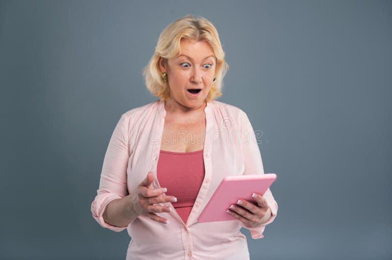 Εύθυμη μέσης ηλικίας γυναίκα που φαίνεται ζαλισμένη μετά από να διαβάσει το μήνυμα στοκ φωτογραφία με δικαίωμα ελεύθερης χρήσης