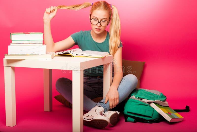 Εύθυμη μαθήτρια μεγάλα eyeglasses που συγκεντρώνονται με στην ανάγνωση β στοκ εικόνες
