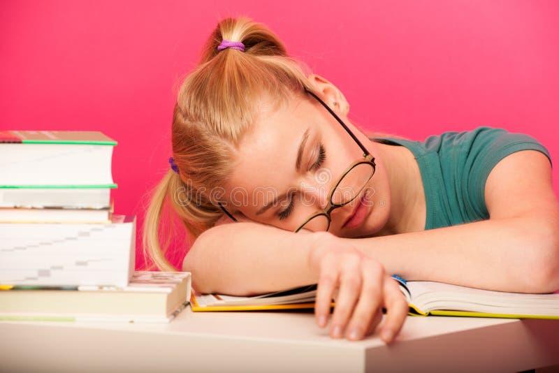 Εύθυμη μαθήτρια με δύο ουρές τρίχας και το μεγάλο eyeglasses sittin στοκ εικόνα