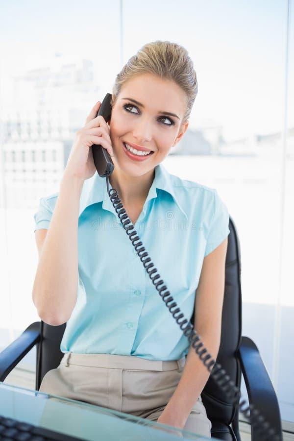 Εύθυμη μοντέρνη επιχειρηματίας που απαντά στο τηλέφωνο στοκ φωτογραφίες