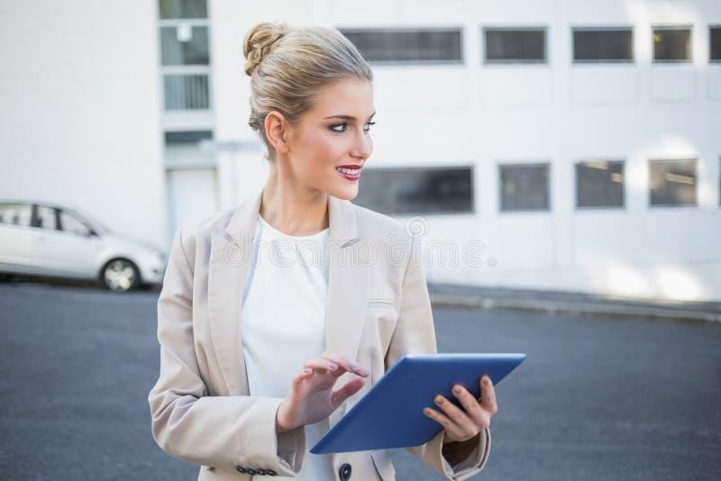 Εύθυμη μοντέρνη επιχειρηματίας που χρησιμοποιεί την ψηφιακή ταμπλέτα στοκ εικόνες