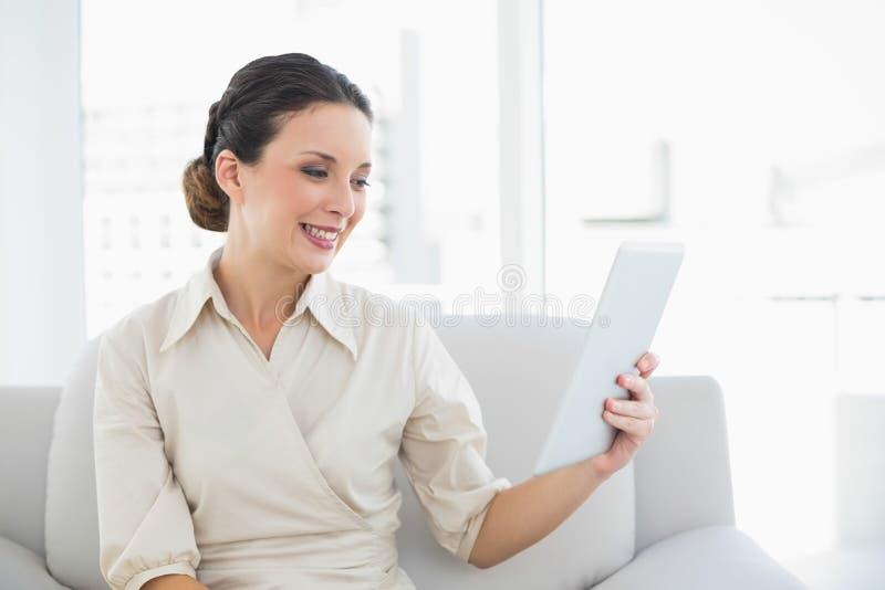 Εύθυμη μοντέρνη επιχειρηματίας brunette που εξετάζει το PC ταμπλετών της στοκ εικόνες