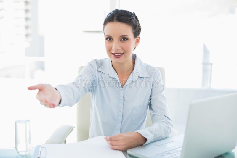 Εύθυμη μοντέρνη επιχειρηματίας brunette που παρουσιάζει το χέρι της στοκ φωτογραφία