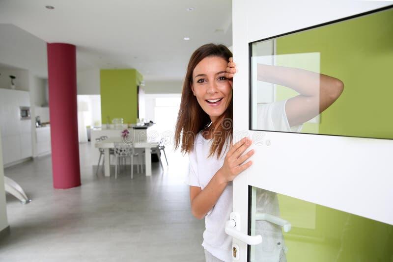 Εύθυμη μπροστινή πόρτα σπιτιών κοριτσιών ανοίγοντας στοκ εικόνες