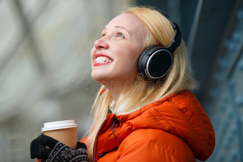 Εύθυμη νέα γυναίκα που ακούει τη μουσική και που απολαμβάνει τον καφέ υπαίθρια στοκ φωτογραφία