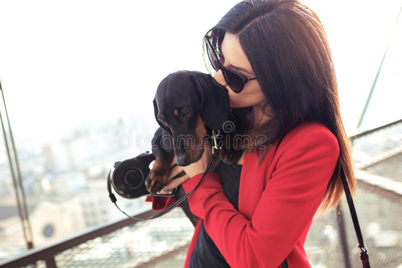 Εύθυμη νέα γυναίκα που κρατά την λίγο σκυλί φιλώντας το στην οδό στοκ εικόνες