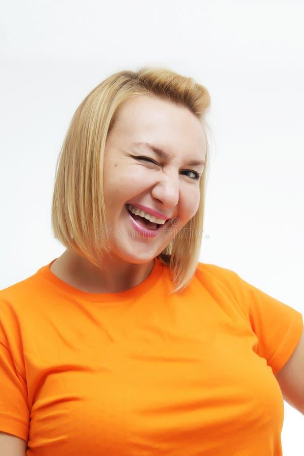Εύθυμη νέα γυναίκα που κλείνει το μάτι πέρα από το άσπρο υπόβαθρο στοκ εικόνες με δικαίωμα ελεύθερης χρήσης