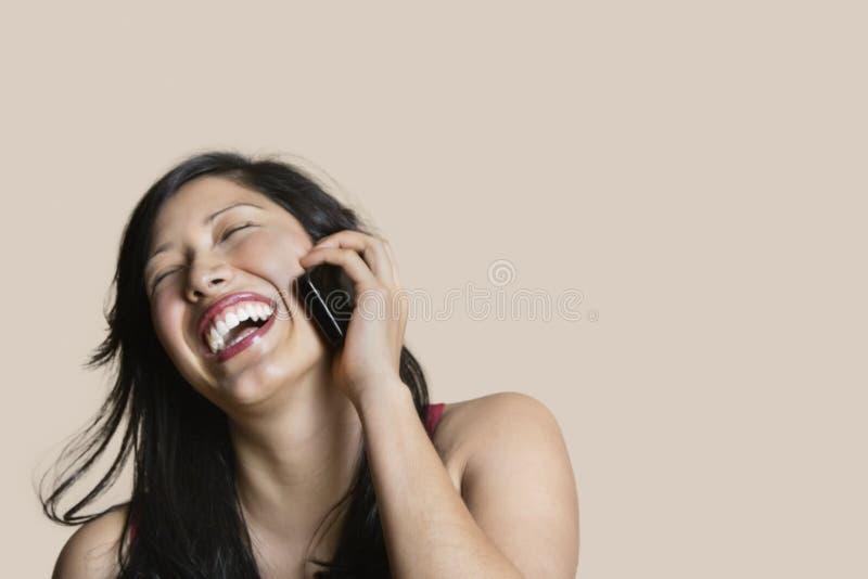 Εύθυμη νέα γυναίκα που μιλά στο κινητό τηλέφωνο πέρα από το χρωματισμένο υπόβαθρο στοκ εικόνες