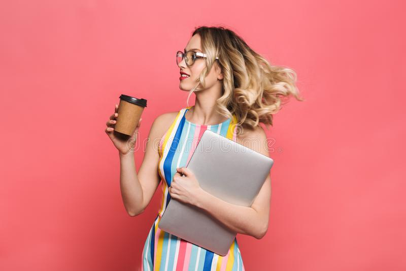 Εύθυμη νέα γυναίκα που φορά eyeglasses τη στάση στοκ φωτογραφία