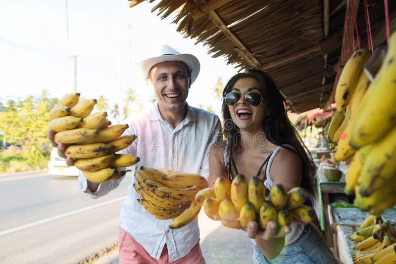 Εύθυμη νέα δέσμη μπανανών εκμετάλλευσης ζεύγους στους ευτυχείς χαμογελώντας τουρίστες αγοράς οδών στα ασιατικά φρούτα Bazaar στοκ εικόνα