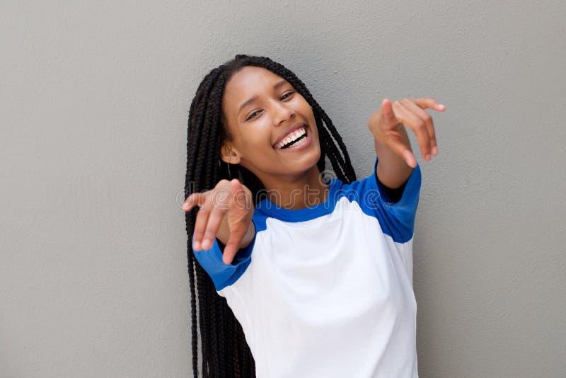 Εύθυμη νέα μαύρη γυναίκα που δείχνει τα δάχτυλα στο γκρίζο κλίμα στοκ φωτογραφίες