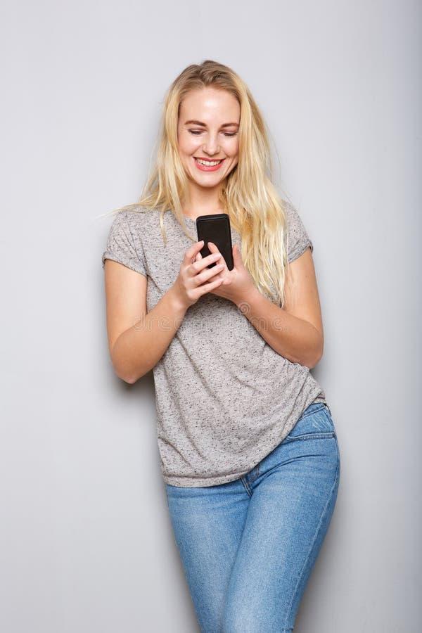 Εύθυμη νέα ξανθή γυναίκα που κρατά το κινητό τηλέφωνο στοκ φωτογραφία