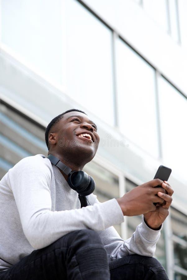 Εύθυμη νέα συνεδρίαση μαύρων έξω με το κινητό τηλέφωνο στοκ φωτογραφίες
