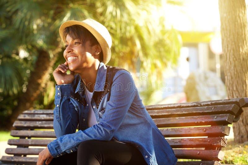 Εύθυμη νέα συνεδρίαση γυναικών αφροαμερικάνων έξω στοκ φωτογραφία