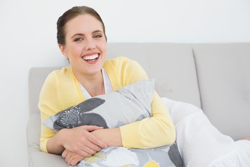 Εύθυμη νέα χαλάρωση γυναικών στον καναπέ στοκ εικόνα