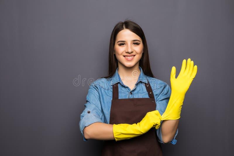 Εύθυμη νοικοκυρά που βάζει στα γάντια πρίν καθαρίζει στοκ εικόνες