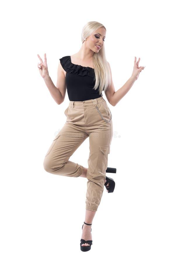 Εύθυμη ξανθή τοποθέτηση γυναικών μόδας πρότυπη σε ένα πόδι που παρουσιάζει χειρονομία νίκης δύο δάχτυλων στοκ εικόνες