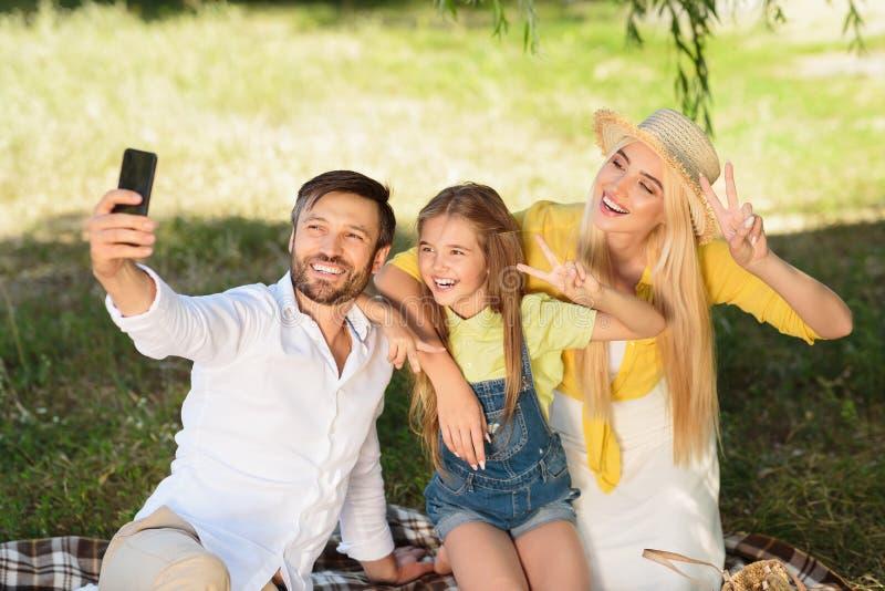 Εύθυμη οικογένεια που κάνει selfie υπαίθρια στο πάρκο στοκ εικόνες