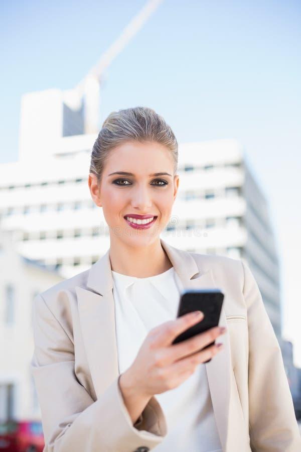Εύθυμη πανέμορφη επιχειρηματίας που στέλνει ένα μήνυμα κειμένου στοκ φωτογραφίες με δικαίωμα ελεύθερης χρήσης