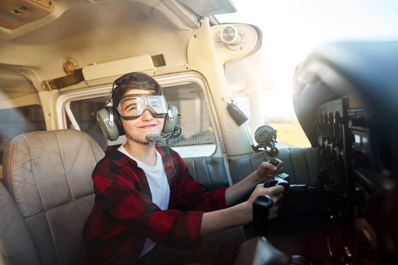 Εύθυμη συνεδρίαση αγοριών στο πιλοτήριο μπροστά από τον πίνακα ελέγχου με τη ρόδα στα χέρια στοκ εικόνα με δικαίωμα ελεύθερης χρήσης