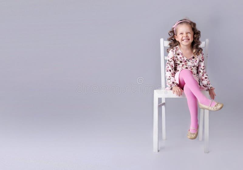 Εύθυμη συνεδρίαση μικρών κοριτσιών στην έδρα με το χαμόγελο στοκ φωτογραφία με δικαίωμα ελεύθερης χρήσης