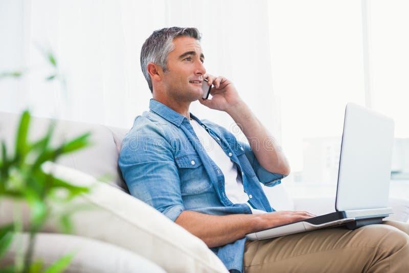 Εύθυμη συνεδρίαση ατόμων στον καναπέ που τηλεφωνά και που χρησιμοποιεί στο lap-top στοκ φωτογραφίες με δικαίωμα ελεύθερης χρήσης