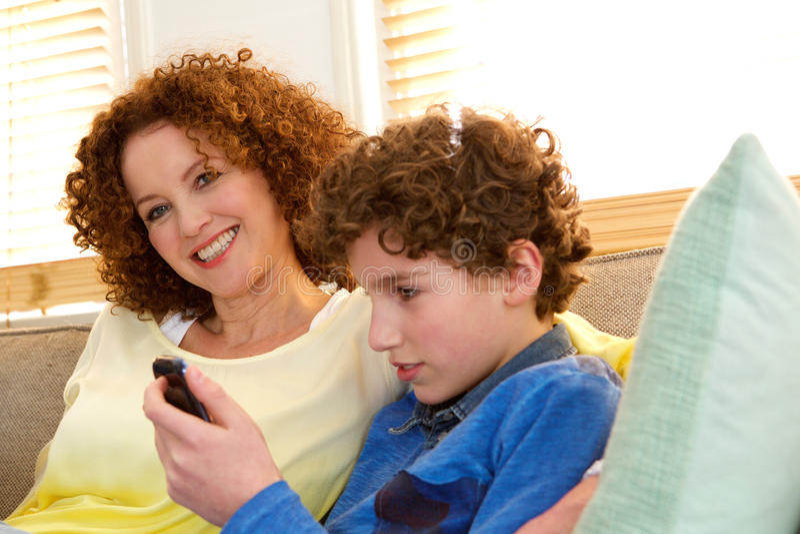 Εύθυμη συνεδρίαση μητέρων με τα παίζοντας παιχνίδια γιων στο τηλέφωνό του στοκ εικόνα