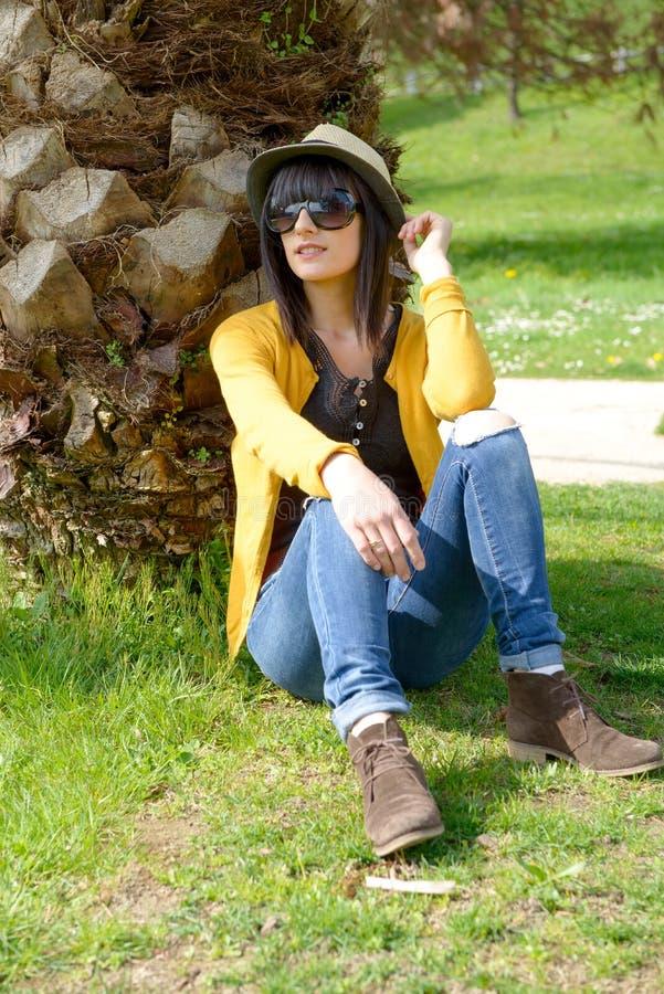 Εύθυμη συνεδρίαση brunette σε ένα δέντρο στο πάρκο στοκ εικόνες