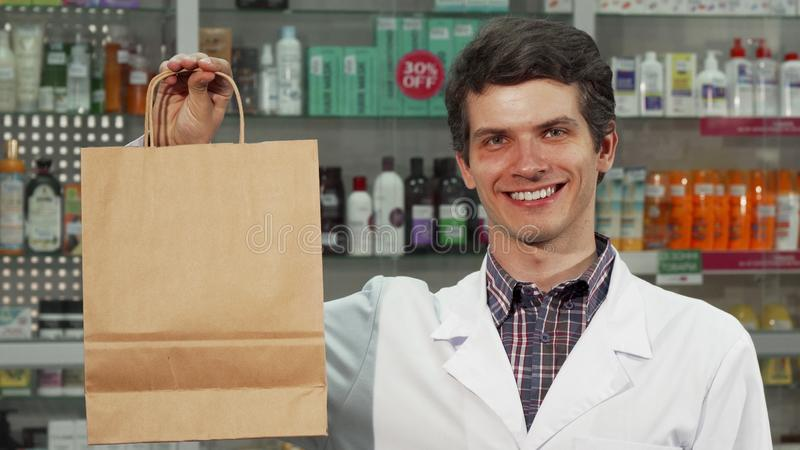 Εύθυμη τσάντα αγορών εκμετάλλευσης φαρμακοποιών που χαμογελά στη κάμερα στοκ φωτογραφίες