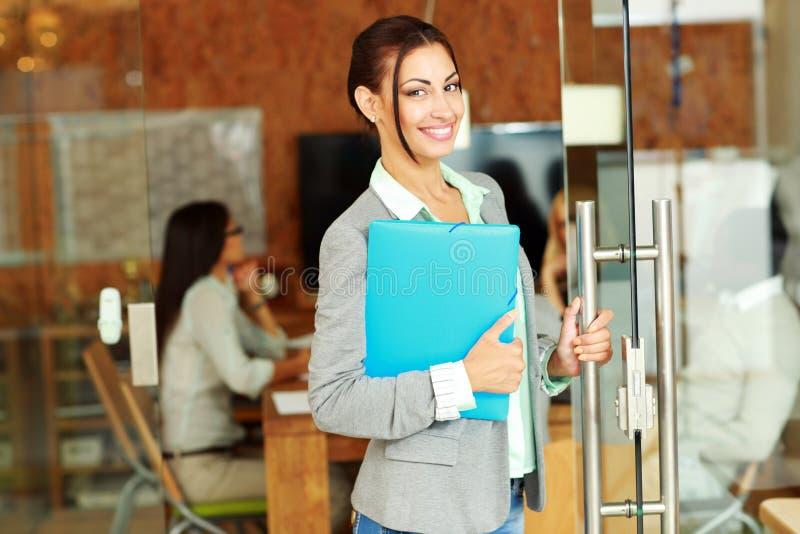 Εύθυμη χαριτωμένη επιχειρηματίας που στέκεται με το φάκελλο στοκ φωτογραφία με δικαίωμα ελεύθερης χρήσης