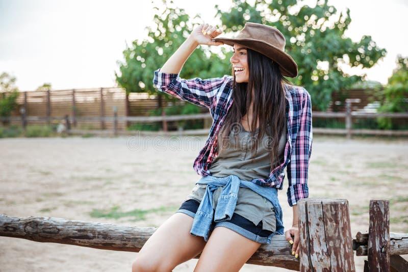 Εύθυμη χαλαρωμένη νέα συνεδρίαση γυναικών cowgirl στο φράκτη και χαμόγελο στοκ εικόνες