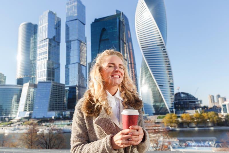 Εύθυμη όμορφη γυναίκα που απολαμβάνει τον καφέ και τη θερμή ηλιόλουστη ημέρα φθινοπώρου στοκ φωτογραφία
