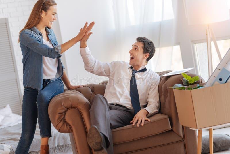 Εύθυμη όμορφη γυναίκα που χαιρετά το συναισθηματικό συγκινημένο σύζυγό της στοκ εικόνες