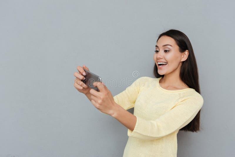 Εύθυμη όμορφη νέα γυναίκα που παίζει τα τηλεοπτικά παιχνίδια στο κινητό τηλέφωνο στοκ φωτογραφίες