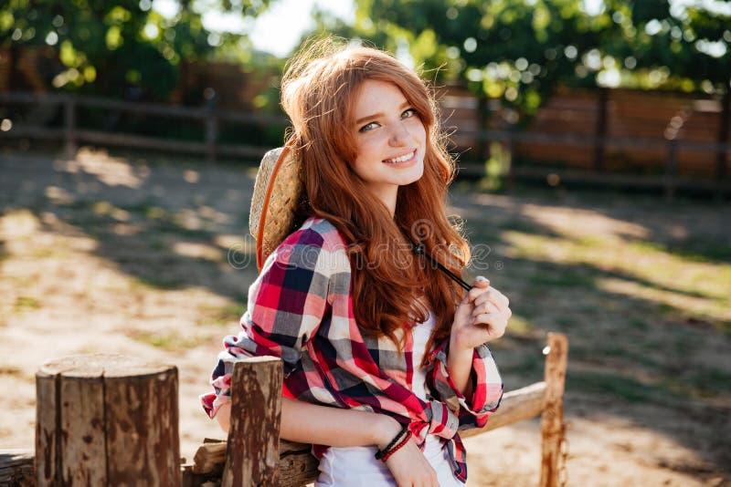 Εύθυμη όμορφη νέα γυναίκα cowgirl στο αγρόκτημα στοκ εικόνες