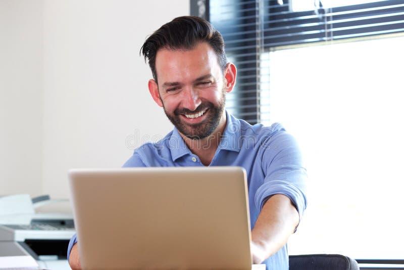 Εύθυμη ώριμη συνεδρίαση ατόμων στο γραφείο του και χρησιμοποίηση του lap-top στοκ εικόνες με δικαίωμα ελεύθερης χρήσης