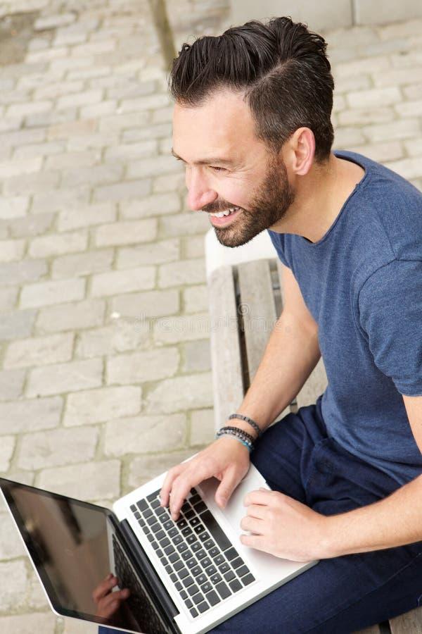 Εύθυμη ώριμη συνεδρίαση ατόμων υπαίθρια με το lap-top στοκ εικόνα