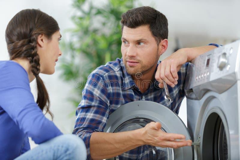 Εύθυμοι γονείς που επιλέγουν το πλυντήριο στοκ εικόνες
