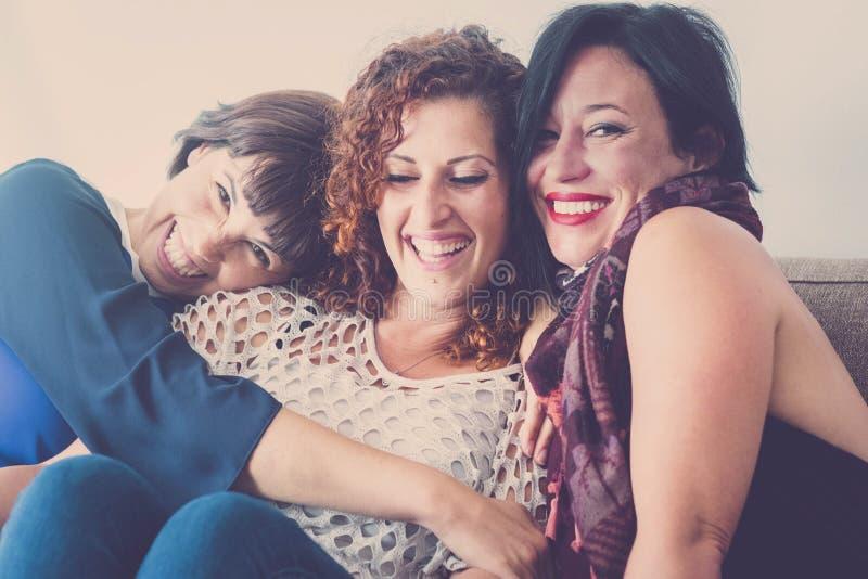 Εύθυμοι θηλυκών φίλοι womane Μεσαίωνα νέοι που κάθονται μαζί σε έναν καναπέ στο σπίτι στη δραστηριότητα ελεύθερου χρόνου εσωτερικ στοκ εικόνα