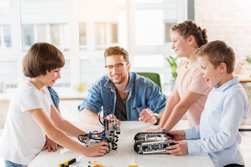 Εύθυμοι νέοι τεχνικοί που χρησιμοποιούν τα παιχνίδια για το παιχνίδι στοκ φωτογραφία