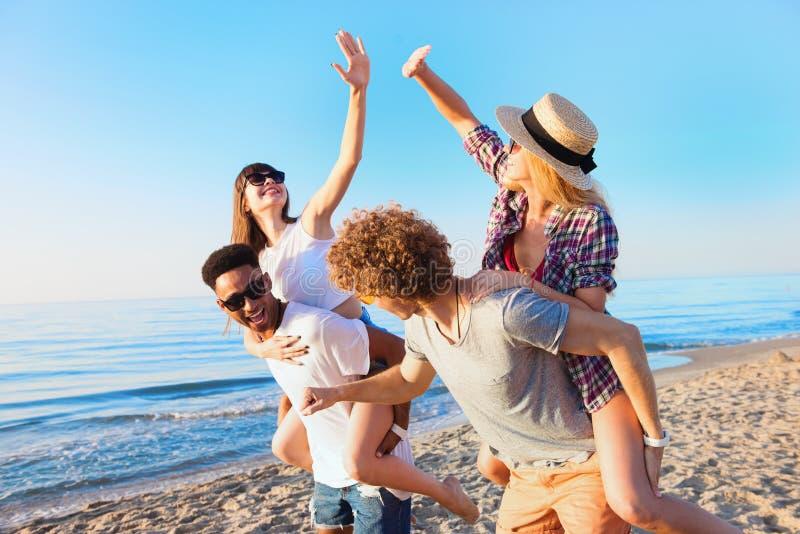 Εύθυμοι νέοι φίλοι που απολαμβάνουν το καλοκαίρι στην παραλία στοκ εικόνα με δικαίωμα ελεύθερης χρήσης