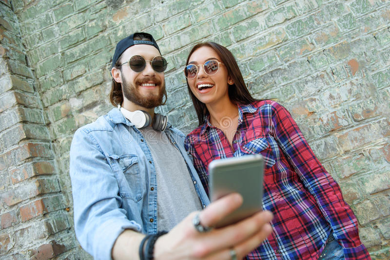 Εύθυμοι τύπος και κορίτσι που χρησιμοποιούν το τηλέφωνο στοκ εικόνα με δικαίωμα ελεύθερης χρήσης