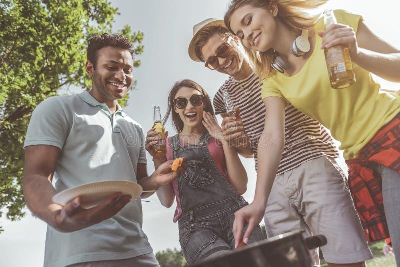 Εύθυμοι φίλοι που προετοιμάζουν τα ψημένα στη σχάρα τρόφιμα στο πάρκο στοκ φωτογραφίες με δικαίωμα ελεύθερης χρήσης