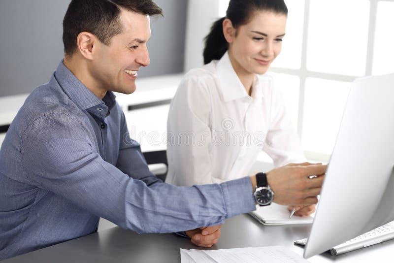 Εύθυμοι χαμογελώντας επιχειρηματίας και γυναίκα που εργάζονται με τον υπολογιστή στο σύγχρονο γραφείο Headshot στη συνεδρίαση ή τ στοκ φωτογραφία