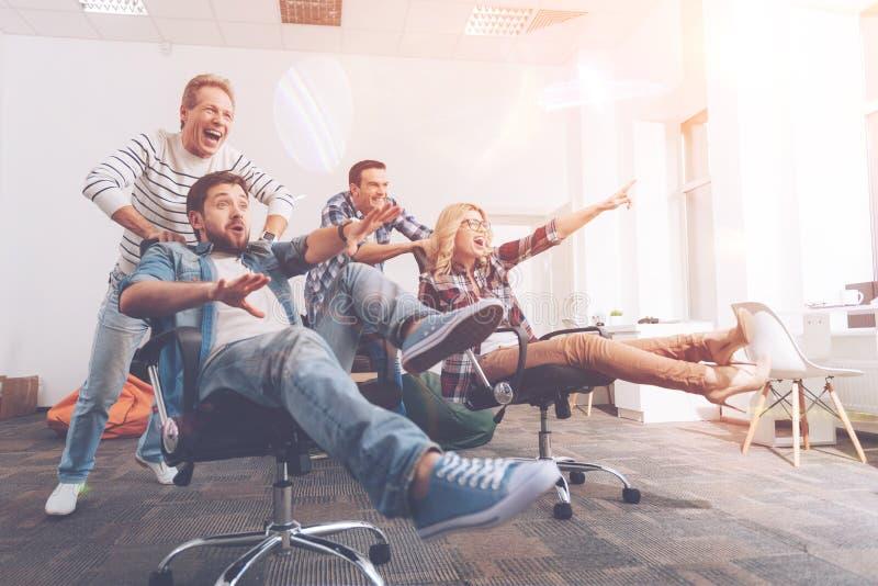 Εύθυμοι χαμογελώντας συνάδελφοι που έχουν το υπόλοιπο στο γραφείο στοκ φωτογραφία με δικαίωμα ελεύθερης χρήσης